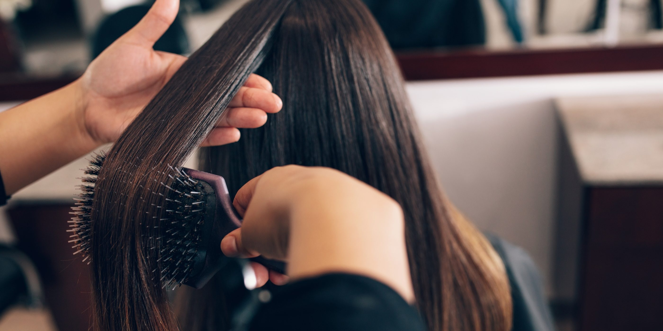Professional hairdresser styling the hair of a customer at salon. Female hair stylist combing hair using a hair brush.